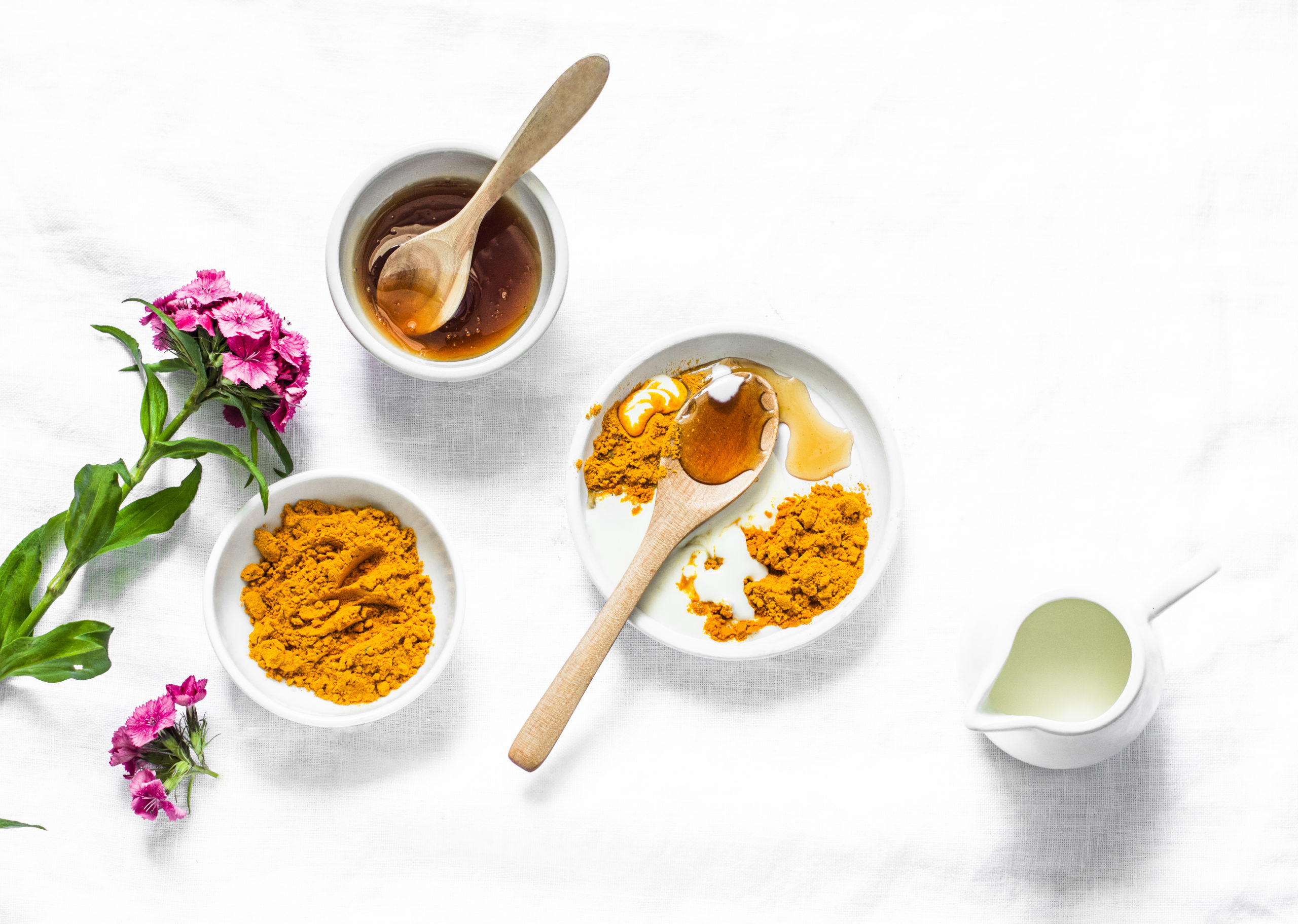 Turmeric, honey, coconut milk face mask. Homemade ingredients beauty products on a light background, top view. Beauty, skin care concept