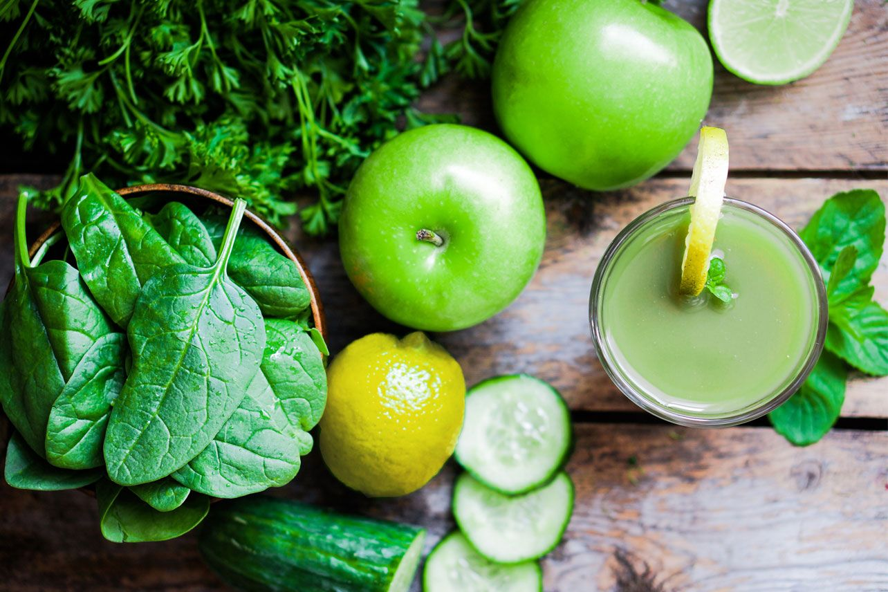 A glass of green smoothie with spinach, green apples, cucumber, and lemons