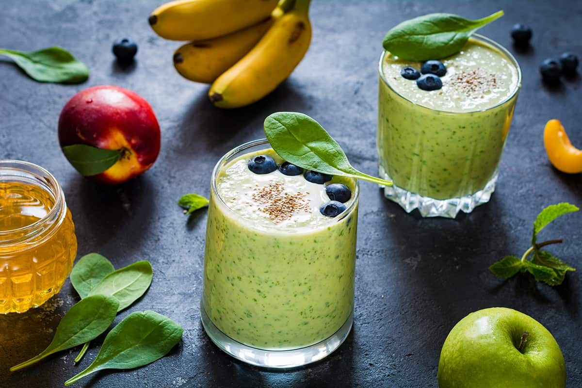 Two green smoothies arranged next to bananas, blueberries, honey, green apples, and a peach