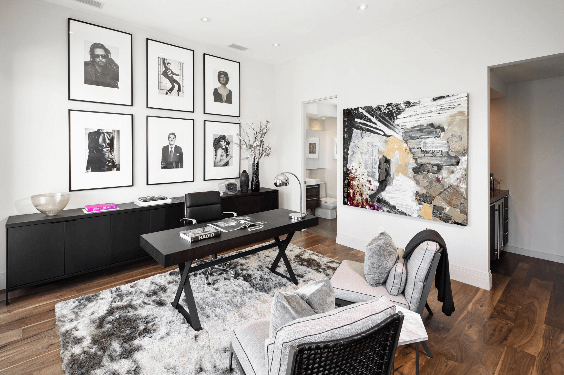 An artistic home office interior in black and white with artwork on the wall