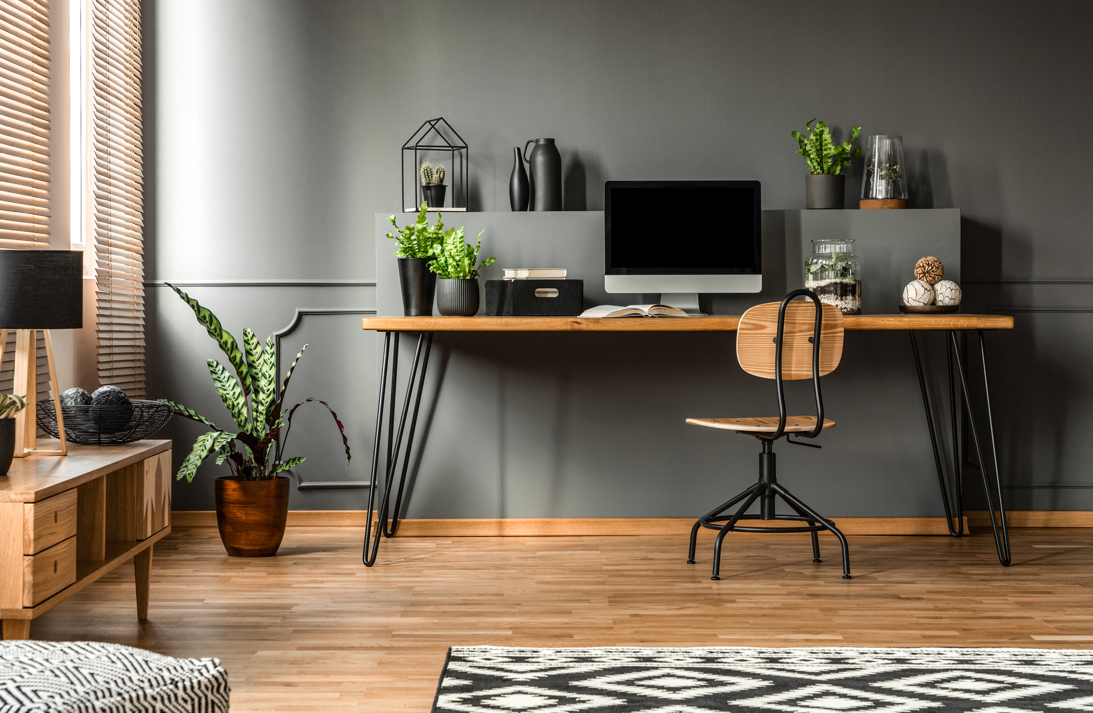 Dark home office interior with wooden desk, chair and computer in the study space in the middle and a rug