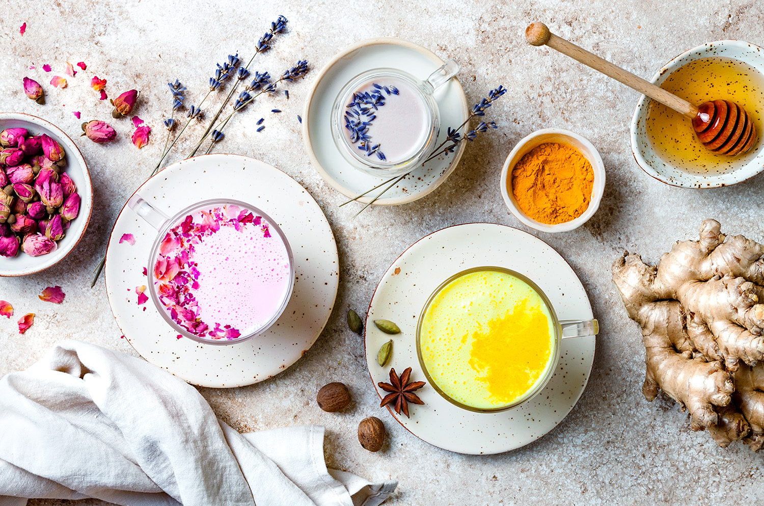 Varieties of moon milk mugs arranged on a counter with turmeric, honey, and ginger