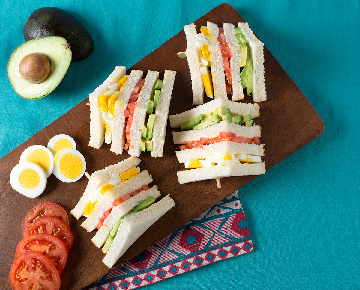 Sandwich triple arranged on a wooden board with avocado, boiled eggs, and tomatoes