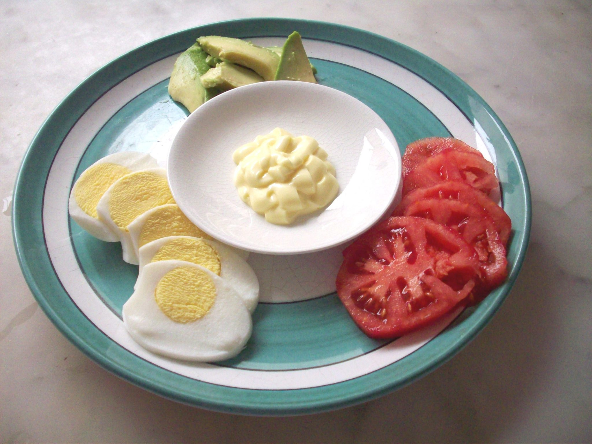 A plate with mayonnaise, sliced tomatoes, avocado, and hardboiled eggs